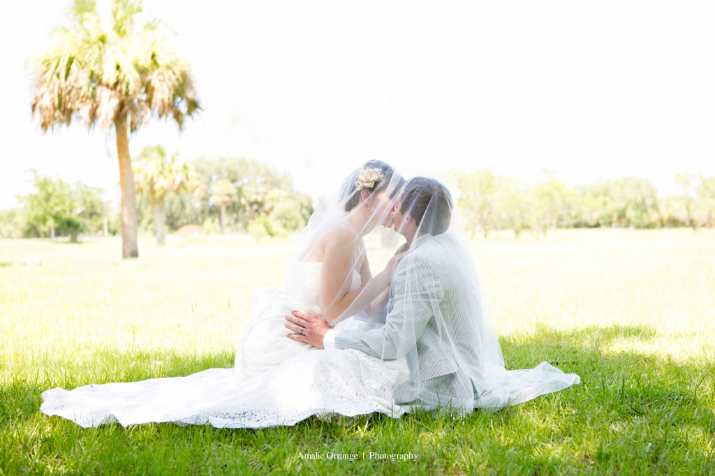 Bride and groom in a field kissing wedding