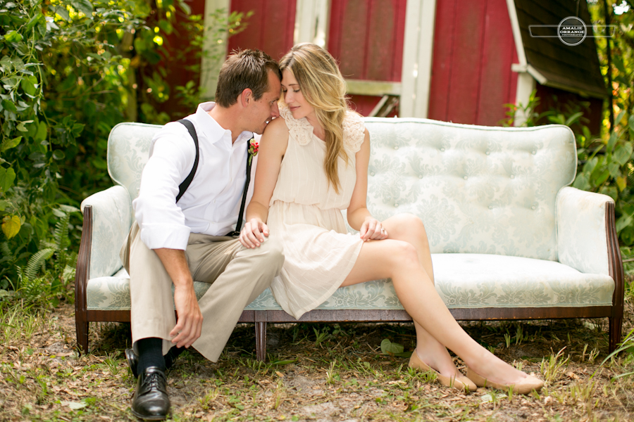 bride and groom on vintage couch in front of rustic barn