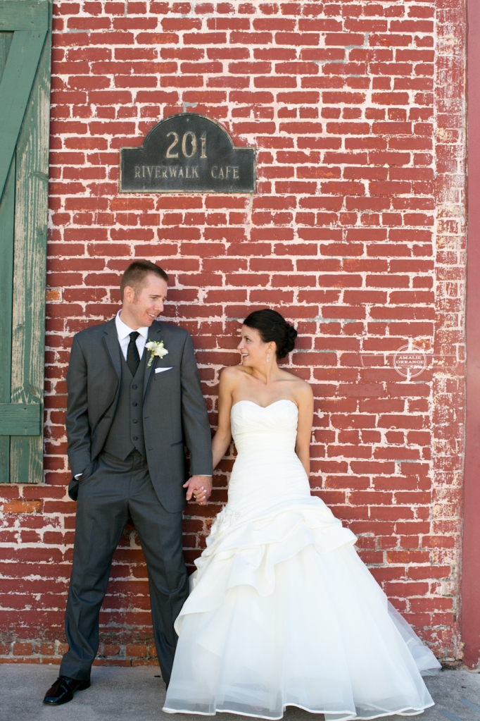 Bride and groom on brick wall
