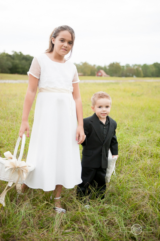 Ring bearer and flower girl in field