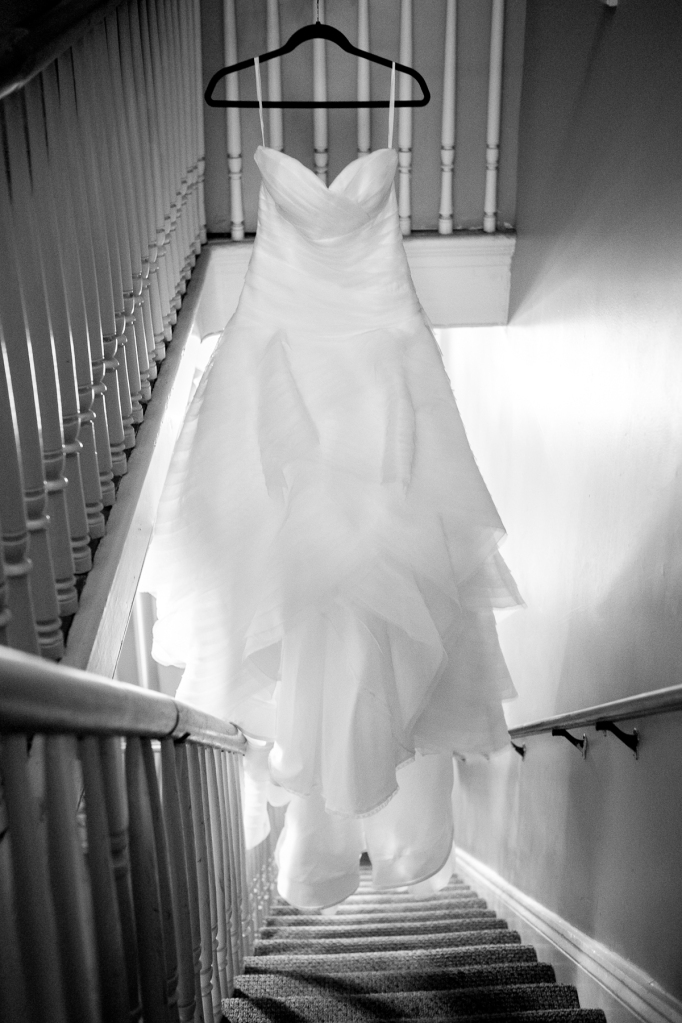 wedding dress hanging in stairwell