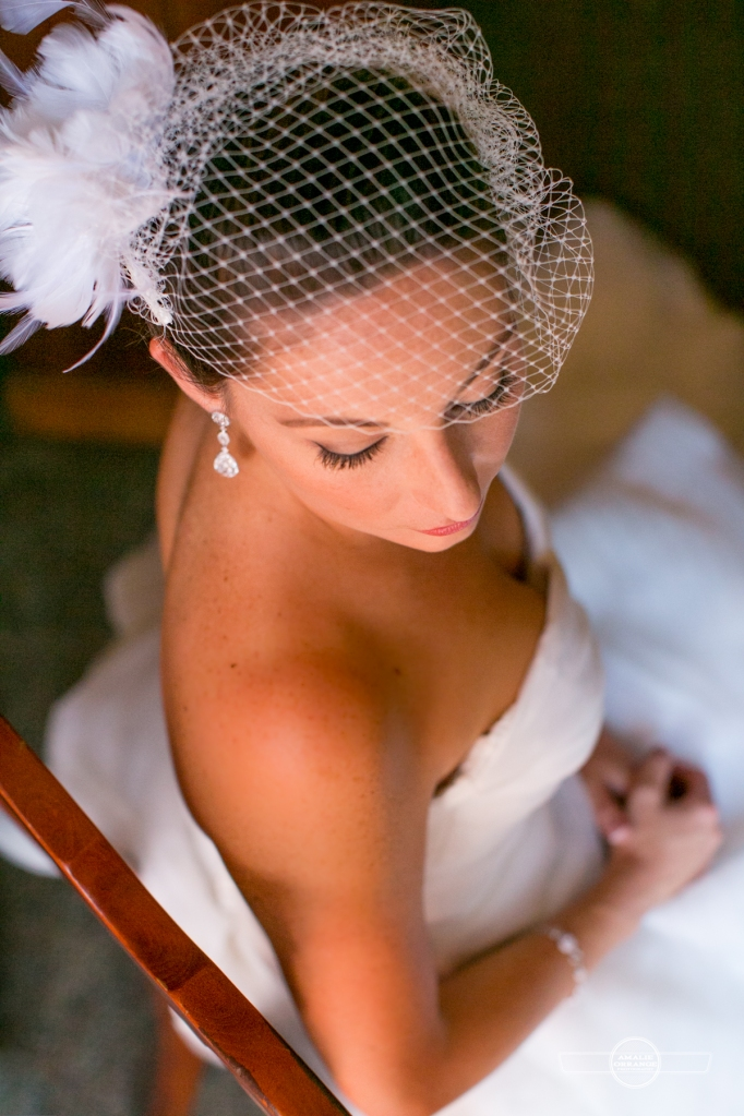 bride sitting in chair with bird cage veil