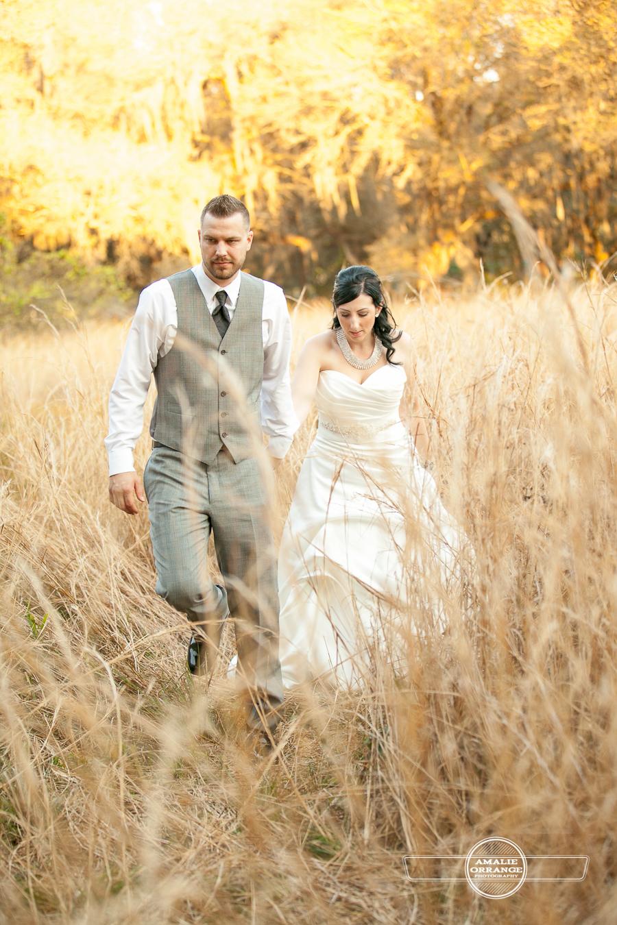 bride and groom in field walking